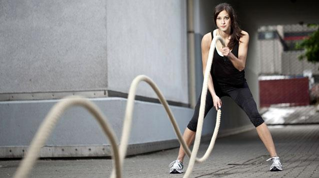 A woman works out with battle ropes.