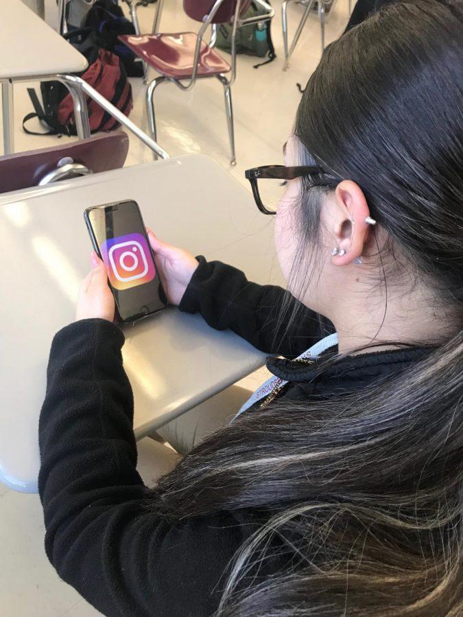 Student scrolling through Instagram.