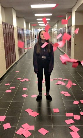 SHS sophomore Cassie Oppelt standing among a pile of excused absence notes.