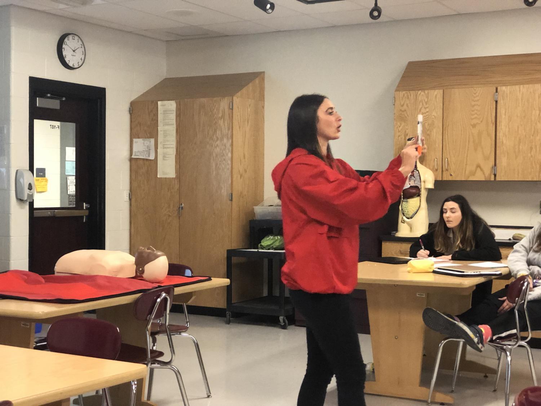 First aid teacher Ms. Sara Davis teaches students how to use an Epi-Pen.