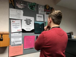 A SHS student analyzing their college options by looking at college flyers on a bulletin board.