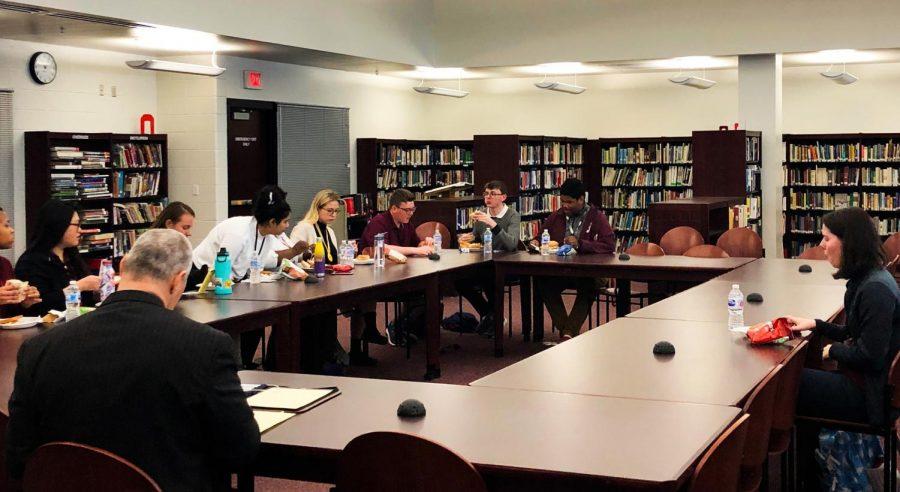 Seniors+gather+around+the+superintendent+to+discuss+school+policies.+