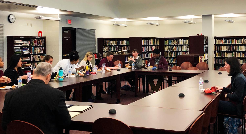 Seniors gather around the superintendent to discuss school policies.