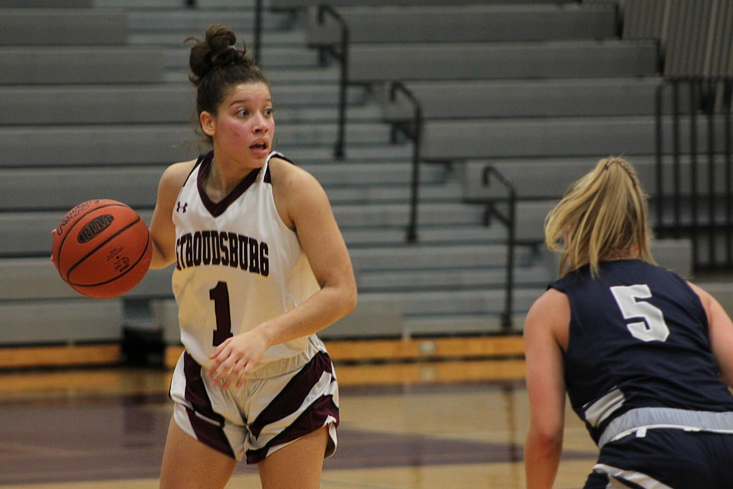 Girls Varsity Basketball player Samantha Columna about to pass the ball to a teammate.