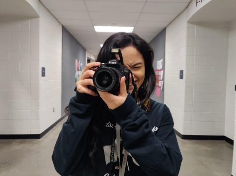 Yearbook photographer junior Julia Gallo is seen above, posing for what she does best: photos.
