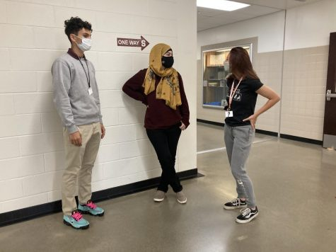 Three stroudsburg students engaging in mask-covered conversation.