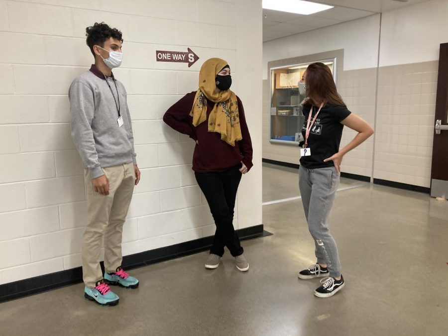Three Stroudsburg students engaging in mask covered and socially distanced conversation.