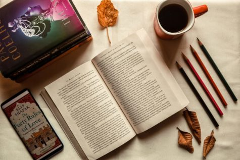 A scene with an open book, coffee, pencils, and leaves scattered around.
