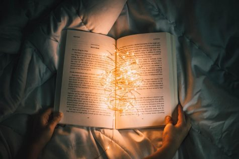 An image of a book illuminated by a string of fairy lights.