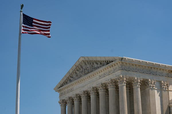 The United States' flag flies over the Supreme Court building on a clear day.