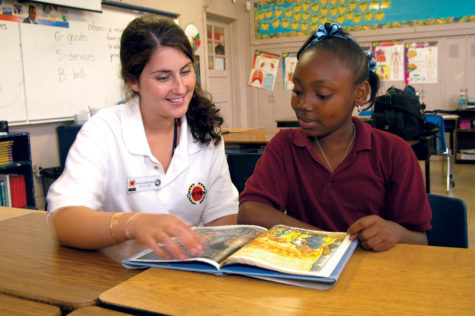 Photo via Flickr.  A teacher helps a student with their work, similarly to the goal of the National Honor Society