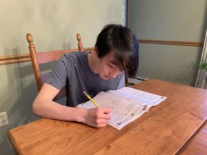 Sophomore Chris Hu prepares for the SAT exam in a practice booklet.