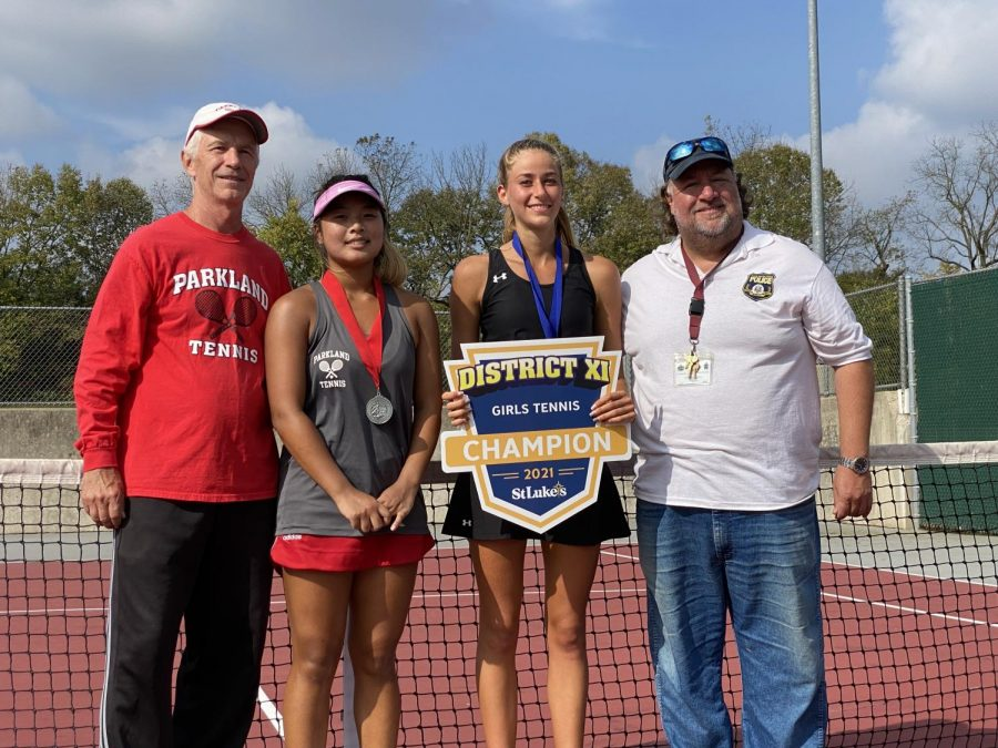 Paraskevi Briegel stands alongside her opponent Erin Joo, left, and coach Gene Taprio, right, as she holds her District XI championship poster.